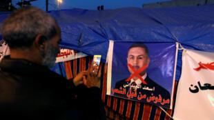 Un manifestante saca una foto de un cartel en contra del candidato a primer ministro Asad al Edan durante las protestas en Bagdad, Irak, este 26 de diciembre de 2019