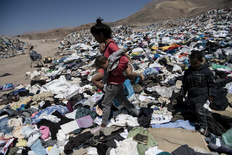 Una migrante venezolana busca en un basurero ropa para ella y sus hijos en el sector de Alto Hospicio, en las afueras de Iquique, Chile, el 26 de septiembre de 2021