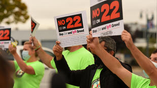 "Rideshare drivers hold signs supporting a ""No"" vote on Proposition 22 in Oakland, California on October 09, 2020"