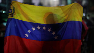 Una mujer sostiene una bandera de Venezuela durante una vigilia el 5 de mayo en Caracas, Venezuela.