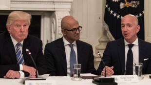 Donald Trump assis aux côtés du PDG de Microsoft Satya Nadella et du patron d'Amazon Jeff Bezos.