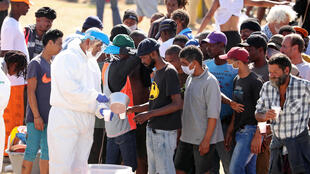 Homeless people queue for food at a camp set up by disaster management authorities during the 21-day nationwide lockdown aimed at limiting the spread of coronavirus disease (Covid-19) in Cape Town, South Africa, April 9, 2020.
