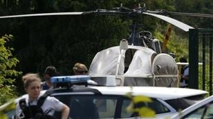 شرطيون أمام المروحية التي استخدمها رضوان فايد في عملية الهروب في 1 يوليو/تموز 2018