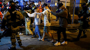 Des manifestants sont escortés par la police hors du campus de l'Université polytechnique de Hong Kong (PolyU) à Hong Kong, le 18 novembre 2019.