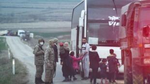 Des militaires transfèrent des migrants de leur camion vers un bus spécialement affrété. Ces migrants ont été refoulés par la police grecque et seront conduits à la station-essence d'Uzunköprü.