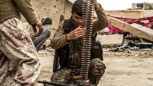 A fighter of the US-backed Syrian Democratic Forces loads an ammunition belt at a position in the village of Baghouz, near Syria's border with Iraq