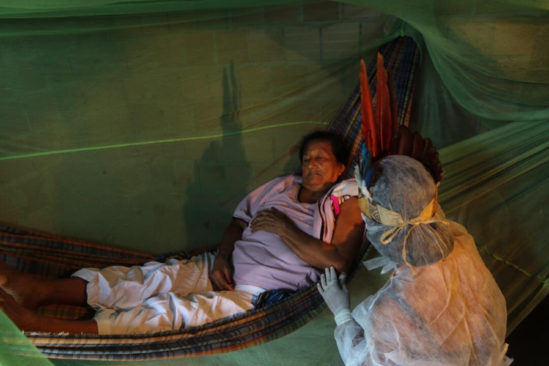 La asistente de enfermería indígena Witoto Vanda Ortega, de 32 años, cuida a un paciente durante una visita de atención médica en el Parque das Tribos, una comunidad indígena en los suburbios de Manaus, estado de Amazonas, Brasil, el 3 de mayo de 2020 durante la pandemia.