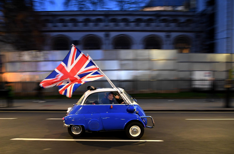 رجل يلوح بعلم بريطانيا وهو يقود سيارته وراء مؤيدي خروج بريطانيا من الاتحاد الأوروبي الذين تجمعوا أمام ساحة البرلمان في وسط لندن في 31 يناير/ كانون الثاني 2020