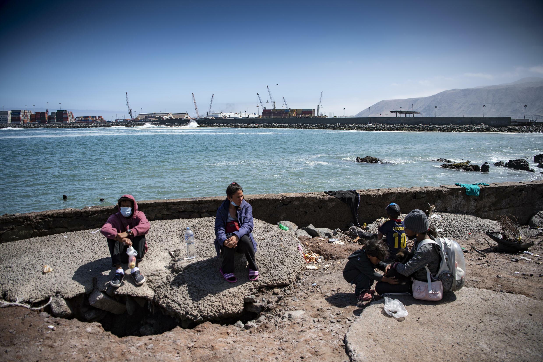 Migrantes venezolanos son vistos en el lugar donde pasarán la noche en Iquique, Chile, el 25 de septiembre de 2021