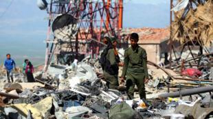 Des combattants kurdes au milieu des ruines d'un site situé près de Derik, au nord de la Syrie, mardi 25 avril.