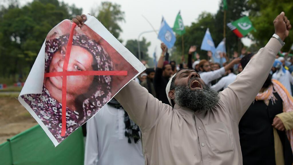 Un manifestant tient une pancarte avec le portrait barré d'Asia Bibi, durant une manifestation contre le jugement de la Cour suprême.