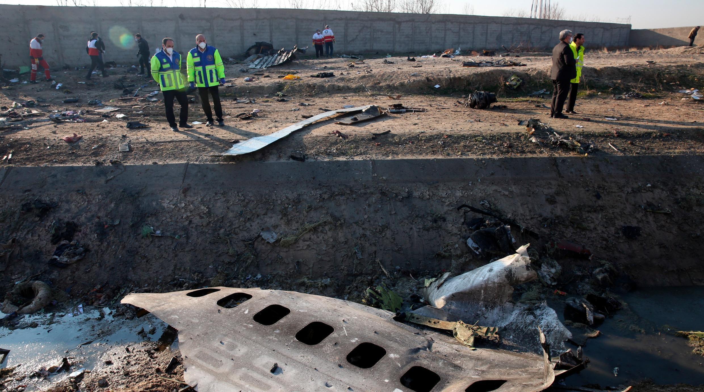 Las autoridades se encuentran cerca de los restos después de que un Boeing 737-800 de Ukraine International Airlines que transportaba a 176 personas se estrelló cerca del aeropuerto Imam Khomeini en Teherán, matando a todos a bordo; en Shahriar, Irán, 8 de enero de 2020 (reeditado el 18 de julio de 2020).