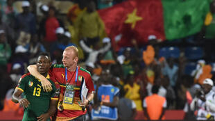Midfielder Christian Bassogog (L) and assistant coach Sven Vandenbroeck celebrate after Cameroon won the 2017 Africa Cup of Nations final against Egypt in Libreville