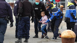 French police, wearing protective masks against the coronavirus, with young migrants picked up off Calais as they tried to get to Britain by boat