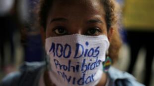 Una manifestante cubre su rostro con un mensaje para recordar los cien días de manifestaciones. 26 de julio de 2018.