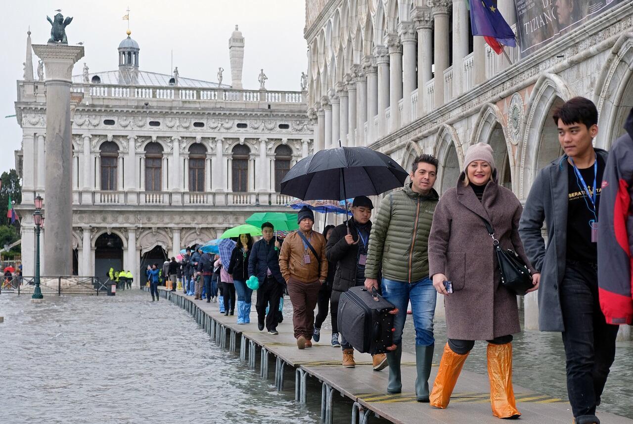 سواح في ساحة سان مارك في البندقية بعد انخفاض مستوى المياه، السبت 17 تشرين الثاني/نوفمبر 2019