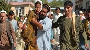 An injured youth is carried to a hospital following a car bomb attack that targeted a government building in the Ghani Khel district of Nangarhar province in Afghanistan on October 3, 2020
