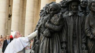 El papa Francisco junto a una estatua de un grupo de migrantes de diversas culturas y de diferentes épocas históricas, en la Plaza de San Pedro en el Vaticano, el 29 de septiembre de 2019.
