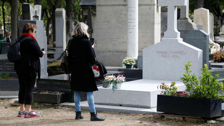 Una mujer toma una foto del lugar donde será enterrado el expresidente francés Jacques Chirac en el cementerio de Montparnasse, en París, el 27 de septiembre de 2019.