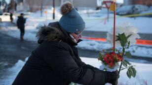 Une passante dépose des fleurs le 31 janvier 2017 à proximité de la mosquée visée par l'attentat.