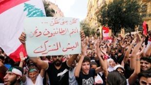 Un manifestante sostiene una pancarta durante una protesta contra el Gobierno en el centro de Beirut. 20 de octubre de 2019.