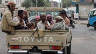 Des hommes armés soutenant le président Hadi à l'arrière d'un pick-up, le 23 mars à Sanaa.