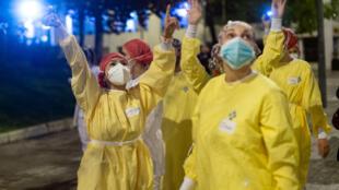 عاملون في مستشفى ببرشلونة يردون التحية على سكان يصفقون لمجهوداتهم في محاربة الوباء