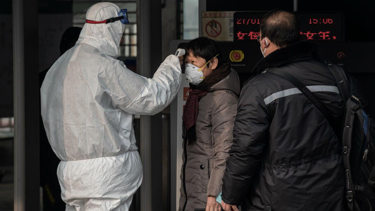 Du personnel de sécurité chinois contrôle la température de passagers à la gare de Pékin, le 27 janvier 2020.