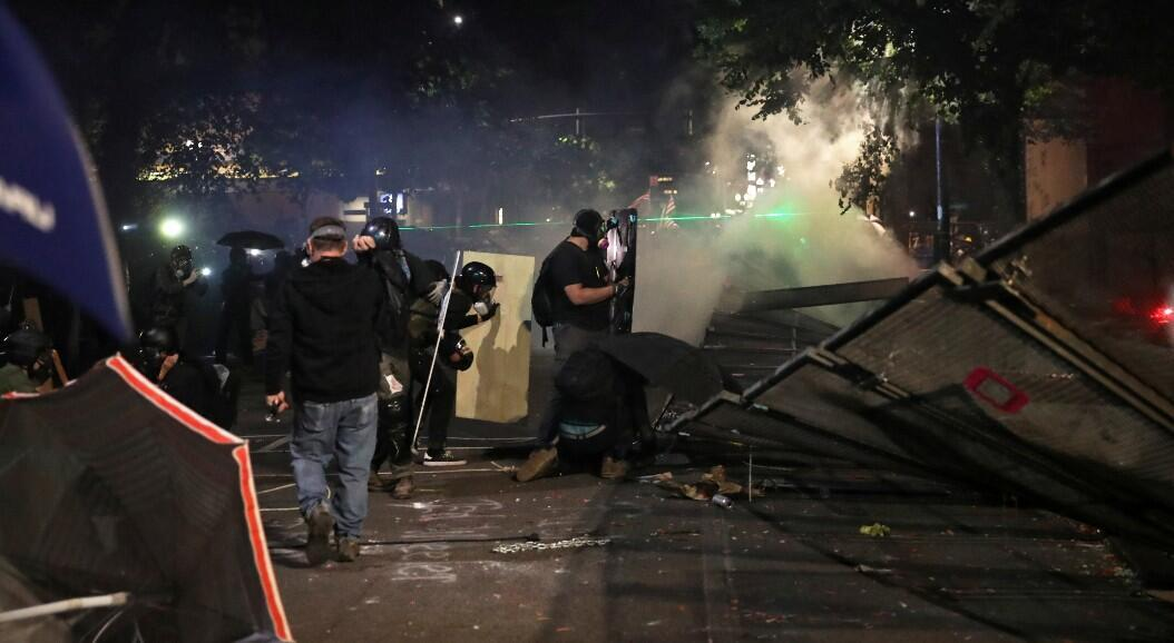 Manifestantes derriban una valla, durante una protesta, en Portland, Estados Unidos, el 26 de julio de 2020.