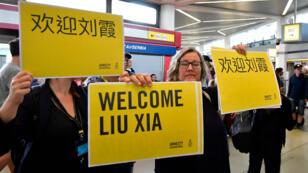 ناشطون من منظمة العفو الدولية يحملون لافتات ترحب بـ ليو شيا، أرملة المعارض الصيني الحائز على جائزة نوبل للسلام ليو شياوبو، التي وصلت إلى مطار تيغيل في برلين 10 يوليو 2018