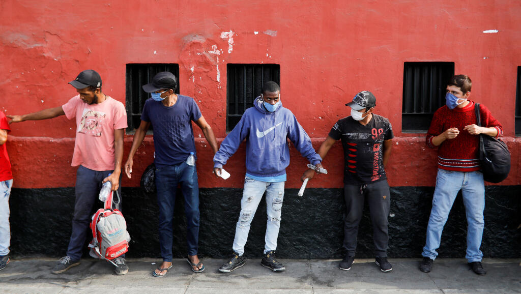 Personas sin hogares esperan a recibir medicamentos en Plaza de Acho, en Lima, Perú, durante la pandemia por Covid-19, el 31 de marzo de 2020.