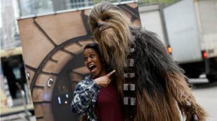 """Una persona vestida como el personaje de Chewbacca de las películas de """"La Guerra de las Galaxias"""", posa para una foto con una admiradora en Manhattan en la ciudad de Nueva York, Estados Unidos, el 4 de mayo de 2018."""
