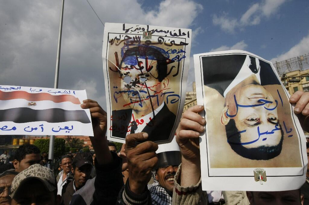 Protesters in Cairo's Tahrir Square hold up defaced posters of President Hosni Mubarak on January 30, 2011.