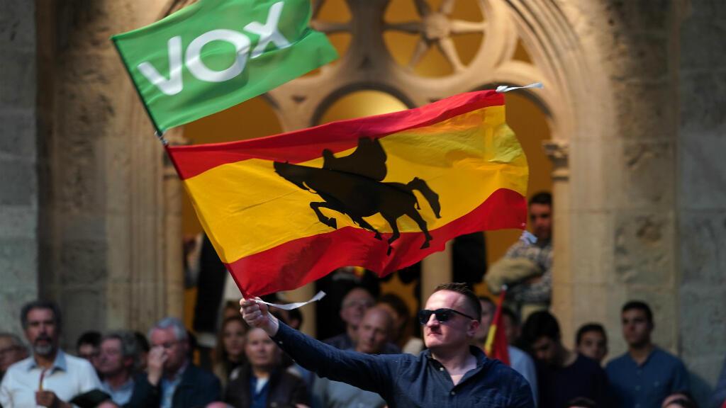 Un hombre ondea una bandera española junto a otra del partido ultraderechista Vox, durante un mitin de campaña del candidato de ese partido, Santiago Abascal, en Burgos, en el norte de España, el 14 de abril de 2019.