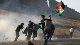 فلسطينيون يحملون جريحا سقط بنيران الجيش الإسرائيلي في الضفة الغربية في 01/08/2015