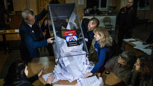 Electoral workers empty a ballot box to start counting ballots in the eastern Ukrainian city of Donetsk on November 2, 2014