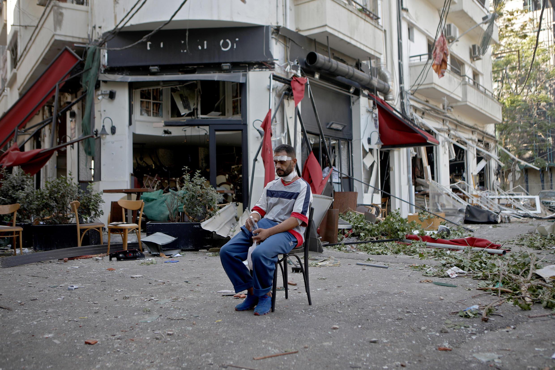 Un homme assis, devant un restaurant au centre de Beyrouth, au lendemain des explosions.