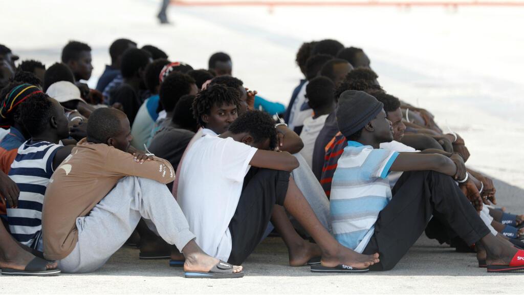 Los migrantes descansan después de llegar con el barco de rescate Eleonore al puerto italiano de Pozzallo, a pesar de la prohibición de las autoridades italianas, Italia, el 2 de septiembre de 2019.
