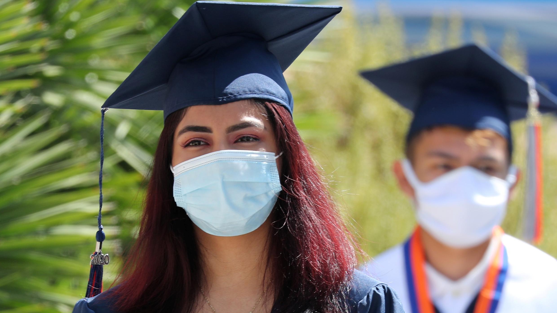 Los estudiantes practican el distanciamiento social mientras hacen fila para tomar fotos en una ceremonia de graduación en una secundaria, en medio del brote de la enfermedad del coronavirus, en Los Ángeles, California, EE. UU., 12 de junio de 2020.