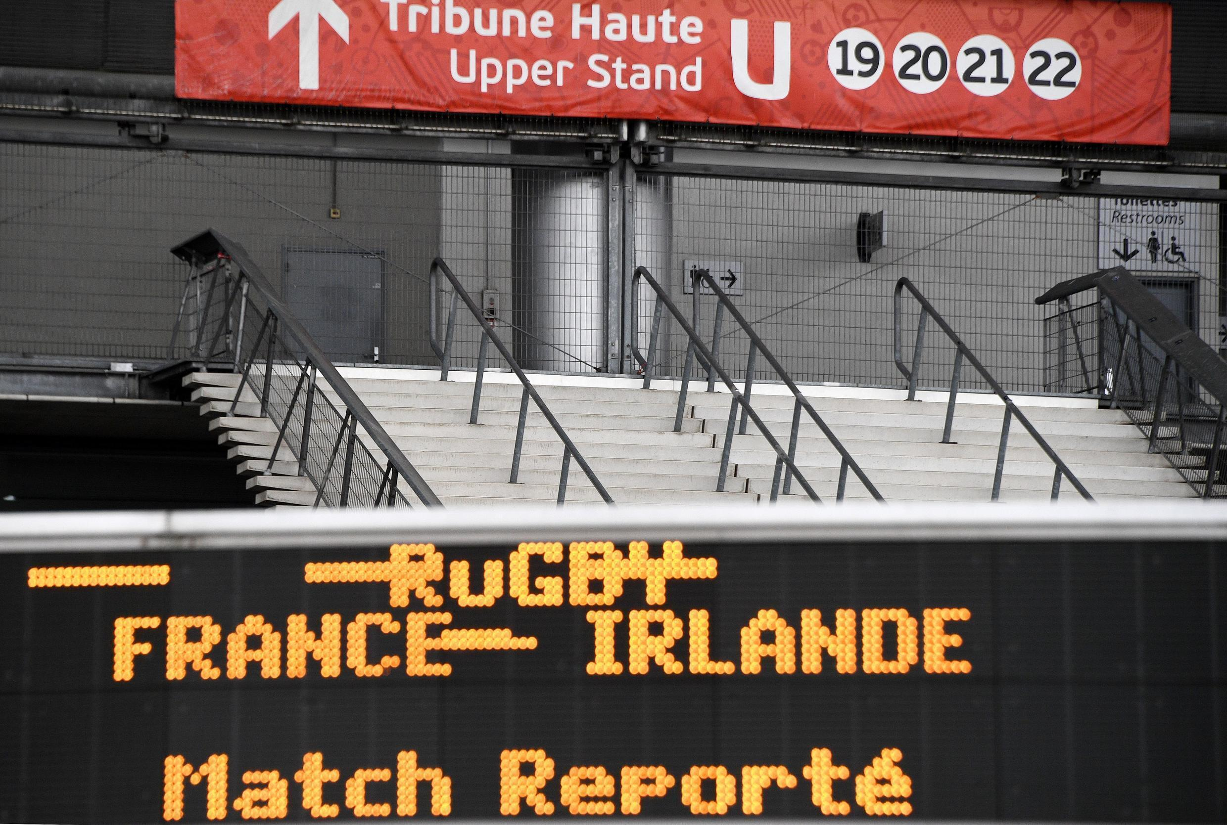 """A photograph taken on March 14, 2020, shows a board reading """"France-Ireland postponed"""" at the entrance to the Stade de France in Saint Denis. This weekend's Six Nations international was postponed due to the coronavirus outbreak."""