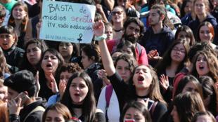 """Los manifestantes gritan consignas con una pancarta que dice: """"Basta de medios sexistas, TV Radio o educación"""", contra el Gobierno durante una manifestación exigiendo el fin del sexismo y la violencia de género en la educación en Valparaíso, Chile el 16 de mayo de 2018."""