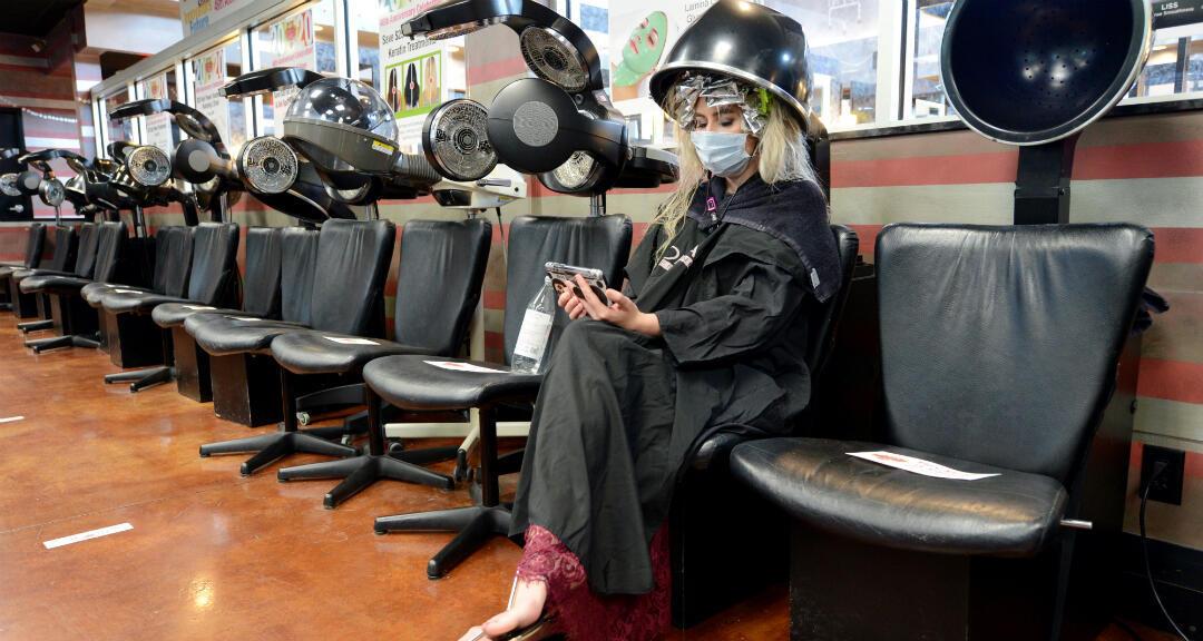 Una clienta se sienta debajo de un secador durante el primer día de relajamiento de las restricciones en Georgia, Estados Unidos, el 24 de abril 2020.