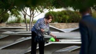 أمريكية تضع زهورا قرب النصب الخاص بضحايا 11 سبتمبر في واشنطن