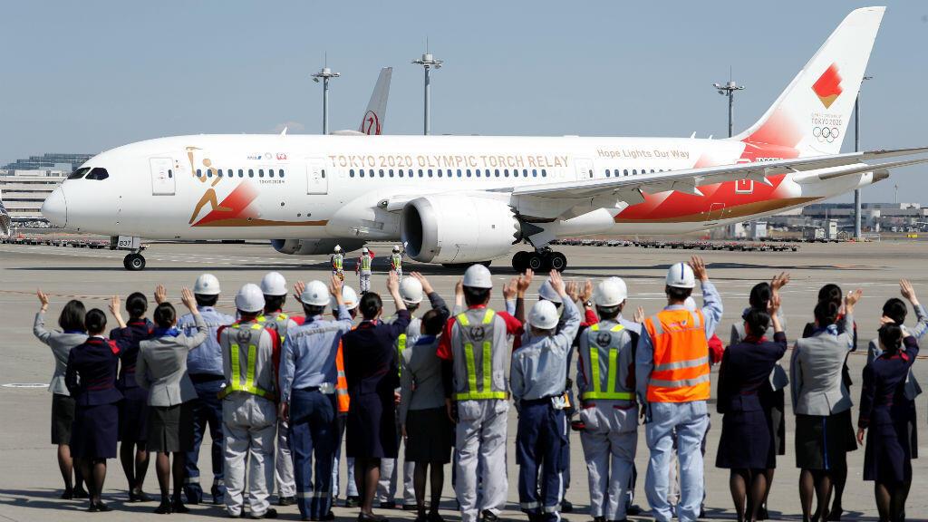 Los miembros del personal de Japan Airlines y All Nippon Airways y la tripulación de la pista saludan cuando ven el avión 'Tokyo 2020 Go', antes de partir hacia Grecia, para transportar la llama olímpica de regreso a Japón, en el aeropuerto internacional de Haneda en Tokio, Japón, el 18 de marzo de 2020.