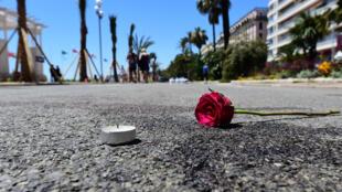 وردة وشمعة وضعتا عند بقعة دم في موقع الهجوم دهسا بشاحنة في مدينة نيس الفرنسية، في صورة التقطت في 16 تموز/يوليو 2016