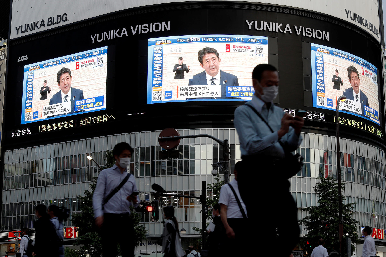 Unas pantallas grandes muestran la conferencia de prensa del primer ministro Shinzo Abe en las que el mandatario anuncia el levantamiento del estado de alerta en Tokio y otras regiones del país. Tokio, Japón, el 25 de mayo de 2020.