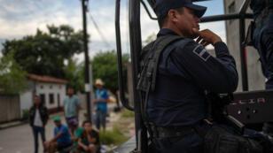 Un vehículo con policías junto a migrantes de América Central, en San Pedro Tapanatepec, México, el 28 de octubre de 2018.