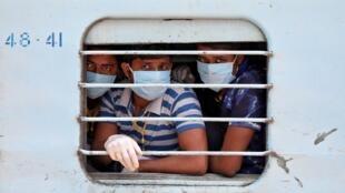 Trabajadores migrantes, que quedaron varados en el estado occidental de Rajastán debido al bloqueo impuesto por el gobierno para prevenir la propagación de la enfermedad por coronavirus, usan máscaras protectoras mientras miran desde la ventana de un tren a la llegada a su estado natal del este de Bengala Occidental, en una estación de ferrocarril en las afueras de Kolkata, India, 5 de mayo de 2020.