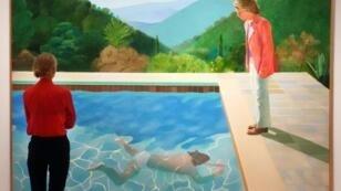 """Una mujer mira """"Retrato de un artista (piscina con dos figuras)"""", una obra de David Hockney que podría convertirse en la más cara rematada de un artista vivo, el 13 de septiembre de 2018 en Christie's en Nueva York"""