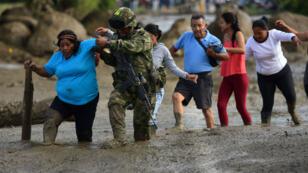 Un soldado ayuda a una mujer después del desbordamiento del río La Paila, en el municipio de Corinto, en Cauca, Colombia.